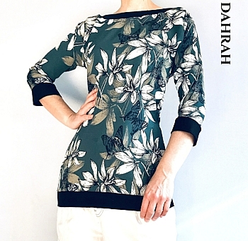 Beautiful Dahrah woman summer blouse with flowers on green background.
